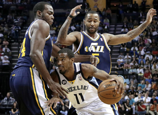 Grizzlies point guard Mike Conley tries to drive past Jazz forward Paul Millsap and guard Mo Williams (5) in the first half Wednesday night in Memphis.