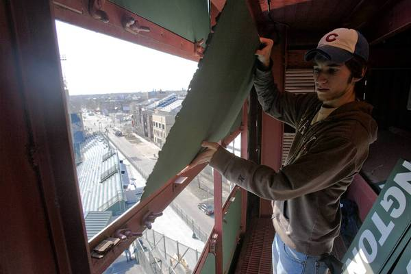 A worker prepares the Wrigley Field scoreboard before a baseball game at the Chicago Cubs stadium in 2007.