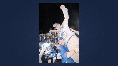 Head coach Phil DeMarco is lifted by son Philip in celebration of Windber's 2008 District 5 Class A football title.