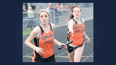 Somerset's Olivia VanDeusen passes the baton to teammate Caroline Heckman in the 4x4 relay Wednesday afternoon.
