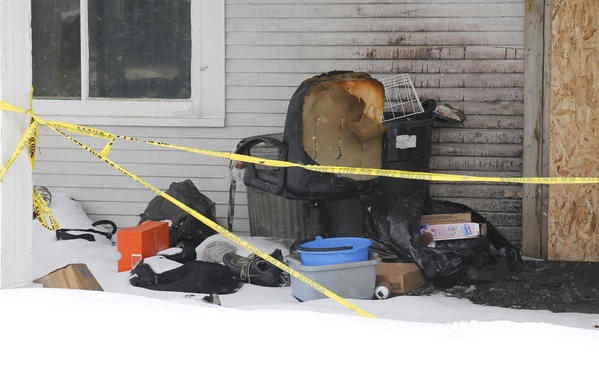 Household items and clothing sit on the porch behind the police tape that surrounds the snow covered remains of the house at 108 Ninth Avenue Southeast that was damaged by fire earlier this month. photo by john davis taken 4/17/2013