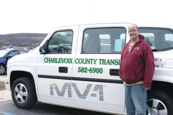 Charlevoix County Transit bus driver Dave Willingham stands in front of one of the service's smaller vehicles. The fleet of 26 buses has already provided more than 60,000 rides in the county the first half of this fiscal year.