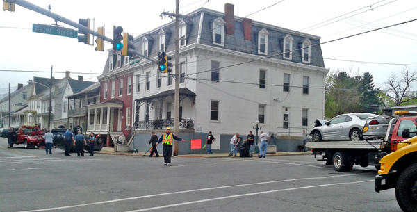Both drivers were taken to Meritus Medical Center after a crash Thursday morning involving a Honda Pilot, on its roof at left, and a Mitsubishi, seen on a two truck at right, at the intersection of Water and Main streets in Smithsburg.