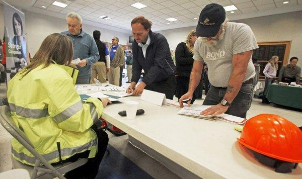 People fill out applications at a job fair in Montpelier, Vt.