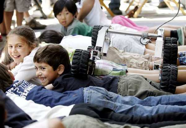 A small rover crawls over children during the JPL Open House in La Canada Flintridge in 2010.