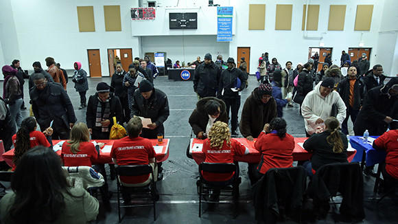 People fill out applications for a CTA customer service assistance job fair at the JLM Abundant Life Community Center in February.