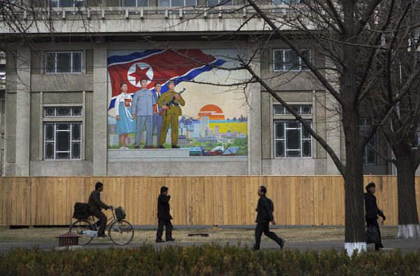 North Koreans pass by a large nationalist painting in Pyongyang.