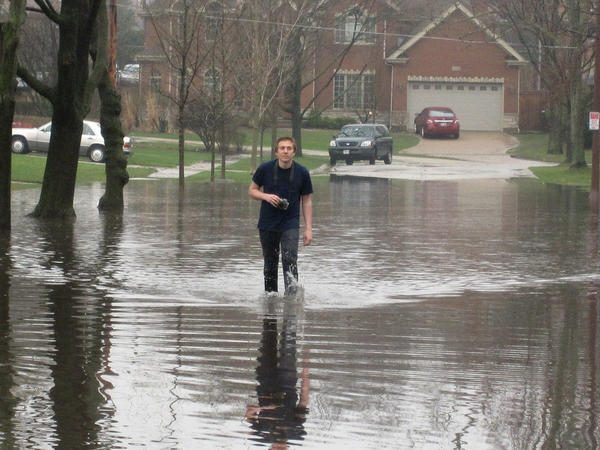 Devin McAllester, 17, wades through the floodwater with his camera around his neck Thursday morning after classes at New Trier High School were canceled due to the rainstorm.