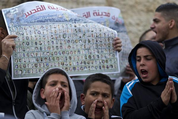 Palestinian children shout slogans before a large poster showing the names of over 100 Palestinians from Jerusalem who are currently held in Israeli prisons during a protest Wednesday at the Damascus Gate in Jerusalem. A critically ill Palestinian prisoner was released Thursday for what Israel said were humanitarian reasons.