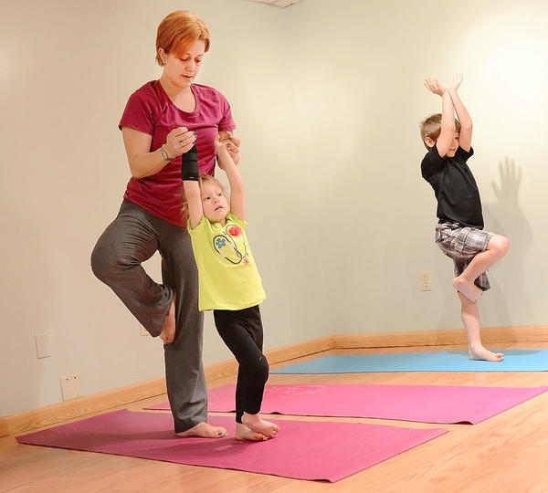 Carlina Weller helps her daughter, Sydnie, with yoga as her son, Greyson, holds a pose family yoga class.