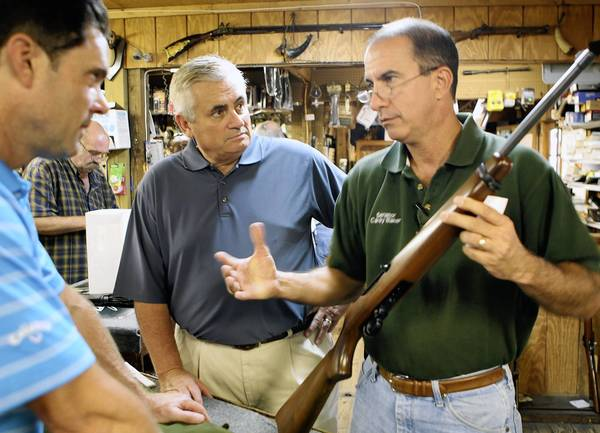 Craig Miller, center , and Carey Baker help John Motsinger of Orlando, left, Monday, August 29, 2011. Miler spent a workday at A.W. Peterson Gun Shop in Mount Dora. Miller, who is running for US Senate, is doing work days through the campaign.