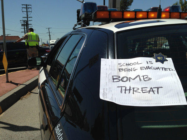 A sign attached to a law enforcement vehicle warns the public of a bomb threat at the Cal State L.A. campus.
