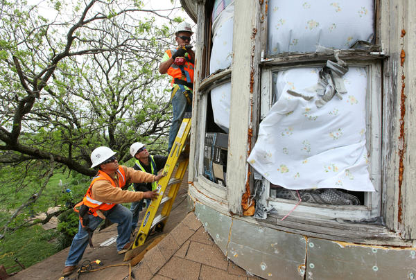 Workers with Johnson Roofing cover the windows of Carol Anne Kocian's home with sheets of plywood following the explosion in West, Texas.