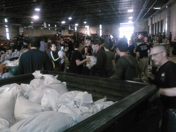 Volunteers load sandbags into a truck Thursday afternoon at the public works department headquarters in Plainfield