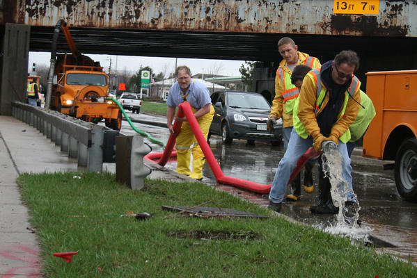 Crews are pumping out water in the 1900 block of Willow Road under a Union Pacific bridge on Thursday afternoon in Northbrook. The road closure, which lasted for most of the day, was one of the most significant ones in the area.
