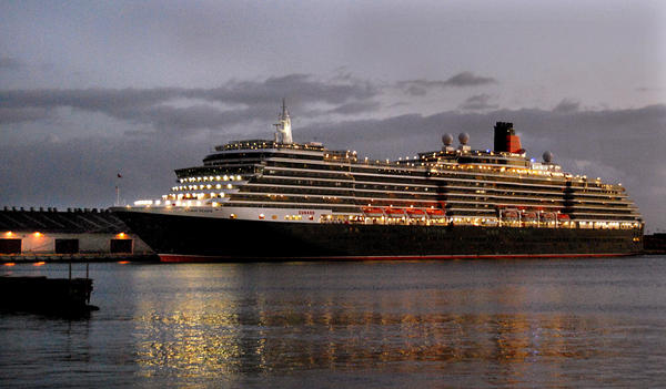 Cunard's Queen Victoria at dusk in port in Honolulu.