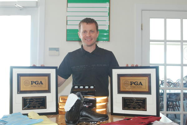Little Traverse Bay Golf Club golf professional John Paul Westbrook displays his two Michigan Section PGA Merchandiser of the Year plaques at the Little Traverse Bay clubhouse. Westbrook was named the states top merchandiser by his peers for the second time in the past three years.