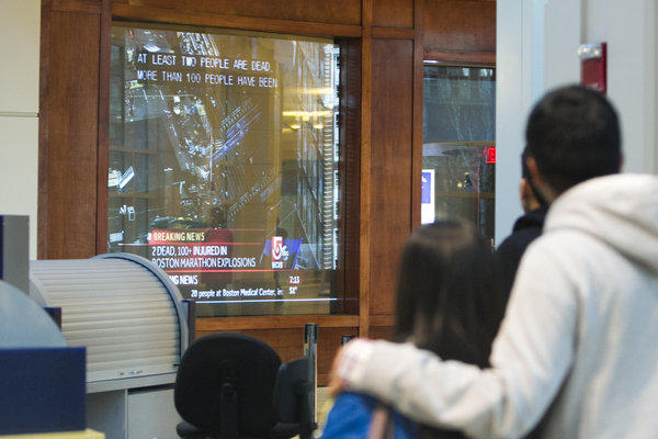People inside the Prudential Center watch news reports after Monday's Boston Marathon bombing.