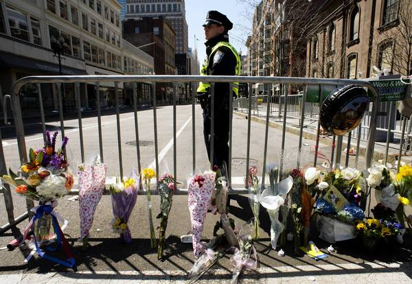 A Boston police officer stands guard at a memorial at Boylston and Arlington streets. The bombings at the Boston Marathon have brought flashbacks of 9/11 to many American Muslims — when they watched the horror in Manhattan and felt attacked as Americans, and then felt attacked for their faith.