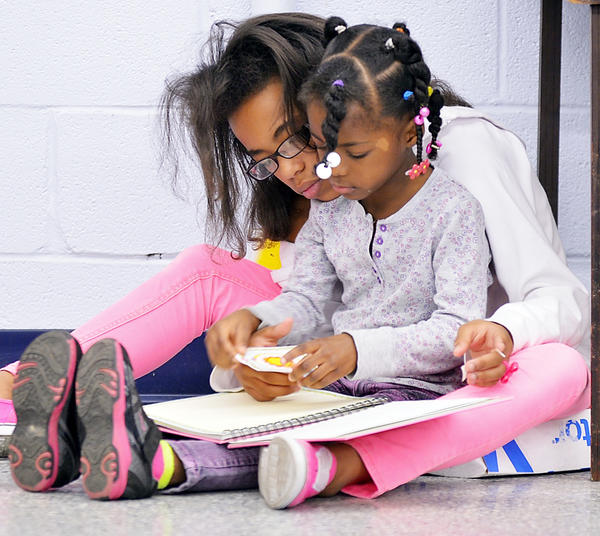 Bianca Giles and Journi Briscoe fill a book with stickers Thursday at the American Association of University Women book sale.