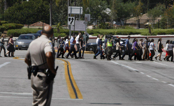 A California Highway Patrol officer watches students and teachers file across North Eastern Avenue at the entrance to Cal State L.A. after university officials evacuated the campus.