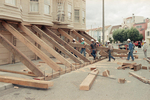 Workers use lumber to shore up a quake-damaged soft-story building in San Francisco's Marina district after the Oct. 17, 1989, Loma Prieta earthquake.