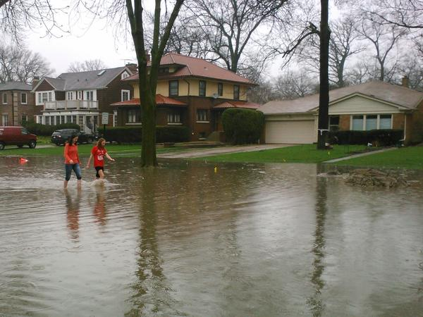 Two girls walk on a flooded Keystone Avenue in River Forest.