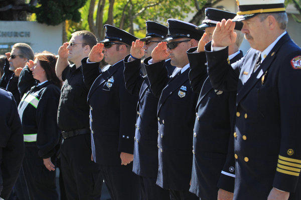 Oakland firefighters salute during funeral services Tuesday for paramedic Quinn Boyer at St. Theresa Catholic Church in Oakland.