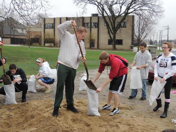 Elmhurst resident Matt MacDonald fills sandbags with help from Elmhurst College student volunteers Payton Robson and Courtney Gleason.