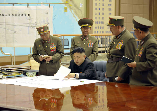 A photo provided by Korean Central News Agency (KCNA) shows North Korean leader Kim Jong Un, center, on March 29, 2013, signing an order putting rockets on standby after an urgent meeting with top generals.