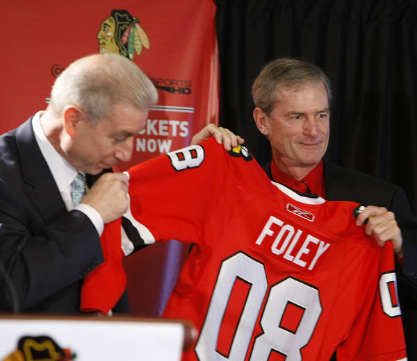 Blackhawks president John McDonough assists Pat Foley with is jersey.