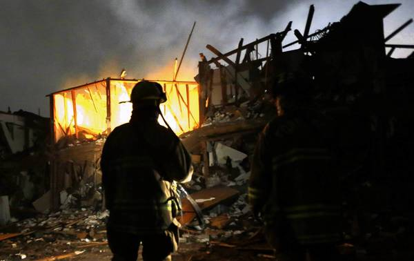 Firefighters use flashlights to search a destroyed apartment complex near the explosion site. In February, the West Fertilizer Co. reported that it had up to 270 tons of ammonium nitrate stored at its plant.