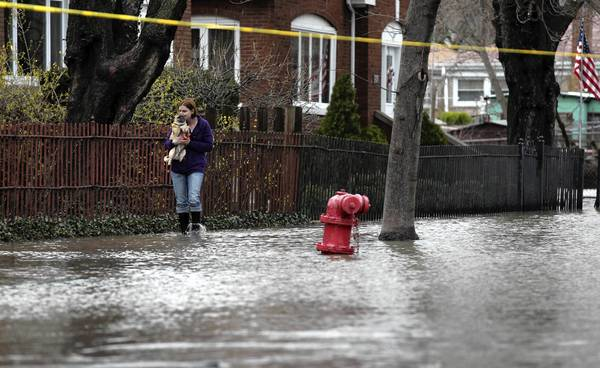 A woman holds her dog while walking through a flooded 4900 block of North Bernard Street in Chicago.
