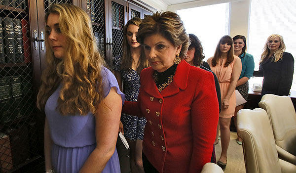 Attorney Gloria Allred, in red jacket, escorts women from a news conference announcing the filing of a complaint against Occidental College.