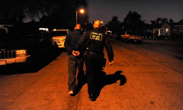 A man is escorted to a vehicle after being arrested by a Department of Justice law enforcement officer in Whittier on suspicion of illegally possessing a handgun.