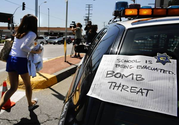 "A Cal State L.A. student runs past a sign taped on a law enforcement vehicle that reads ""School is being evacuated. BOMB THREAT."" School administrators ordered the campus cleared, but many students said directions were not clear and chaos ensued."