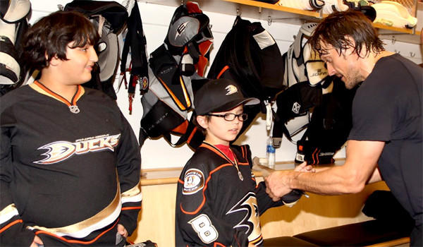 Faryan Heravi, center, and his older brother, Rayan, left, visit with the Anaheim Ducks' Teemu Selanne in the Ducks locker room after a recent game.