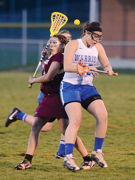 Boonsboro's Olivia Lohman, right, battles to hold off a Brunswick opponent while the ball pops loose during the Warriors' 7-3 victory over the Railroaders.
