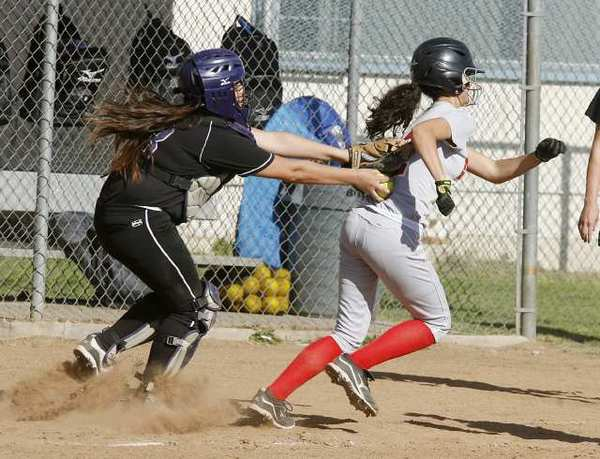 Hoover's catcher Jenesy Gonzalez, left, tags Glendale's Alex Howard in a Pacific League softball game the Nitros won, 11-5.