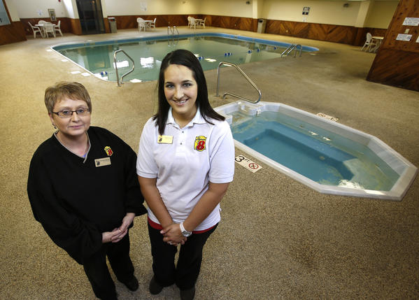 Brenda Habeck, general manager, left and Kelsey Reis, assistant manager, right, at Super 8 East in Aberdeen, stand in the pool and hot tub area of the hotel.