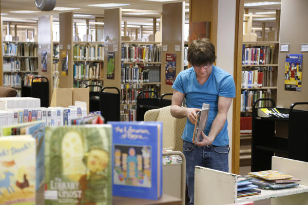 Matt Stoebner, a library technician at the Alexander Mitchell Public Library, shelves books in the children's section Thursday. The children's books are located on the main floor of the library near the front desk, making for close quarters.