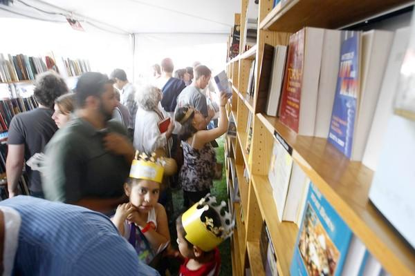 Visitors look over books to purchase at the $5 or Less Book Store tent at the Los Angeles Times Festival of Books at USC on April 22, 2012.