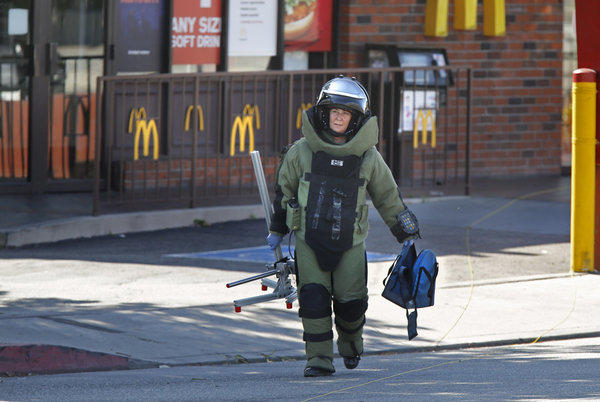 A Los Angeles County Sheriff's Bomb Squad member carries an empty backback from a McDonalds restaurant near the campus of Cal State L.A. on Thursday afternoon.