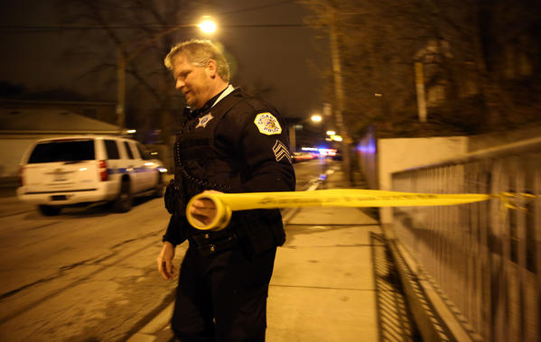 A police sergeant tapes off the 3900 block of North Avondale Avenue after a shooting incident Friday, April 19, 2013, in Chicago.