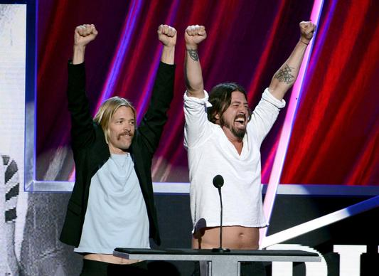 Presenters Taylor Hawkins and Dave Grohl of Foo Fighters, displaying their musical enthusiasm, speak onstage at the 28th Rock and Roll Hall of Fame induction ceremony at Nokia Theatre L.A. Live.