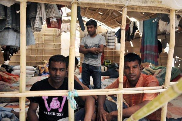 Migrant workers sit inside a makeshift camp in Manolada, Greece.