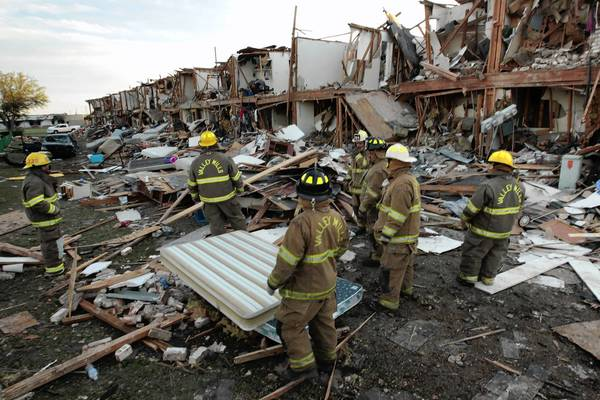 Valley Mills Fire Department personnel walk among the remains of an apartment complex next to the fertilizer plant that exploded yesterday afternoon in West, Texas.