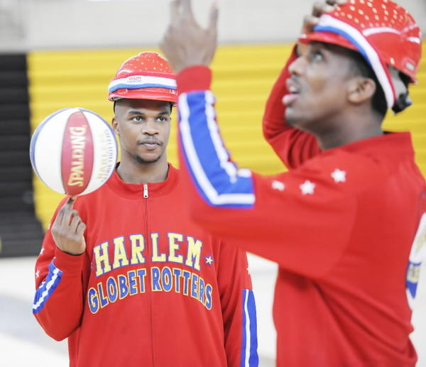 Harlem Globetrotter Jet Williams, left, spins a ball on his finger while watching his teammate, Bull Bullard.