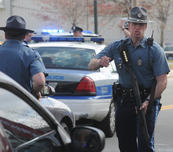 A Massachusett State Trooper pushes media back during a tense moment in the Watertown, Mass., manhunt for a suspect in the Boston Marathon bombings.
