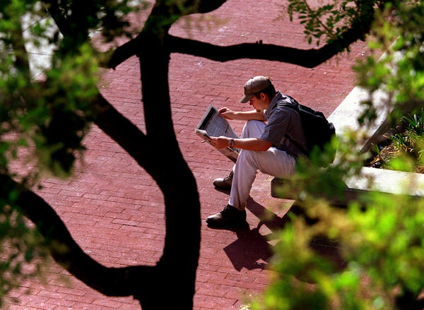 A UC Irvine student reads a copy of the campus newspaper New University between classes.